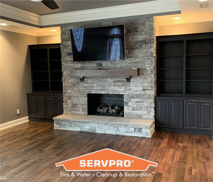 Stone fireplace with built in shelving around it, mounted TV, and tan walls. SERVPRO logo at bottom of the photo.