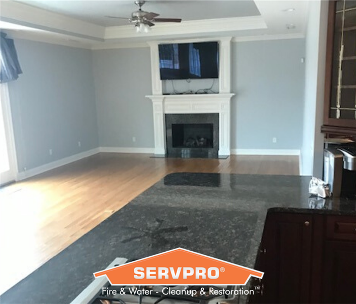 Living room with white fire place and blue walls. SERVPRO logo at the bottom of the photo