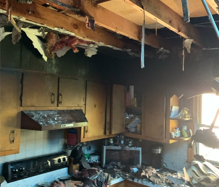 Photo of kitchen destroyed by a fire. Wood falling from the ceiling, burnt items everywhere, and soot covering everything