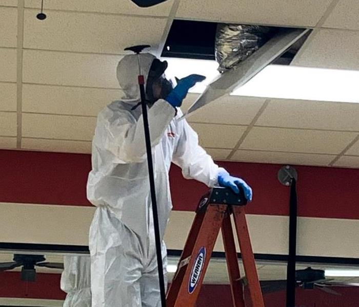 SERVPRO employee working on cleaning air ducts while wearing full personal protective equipment