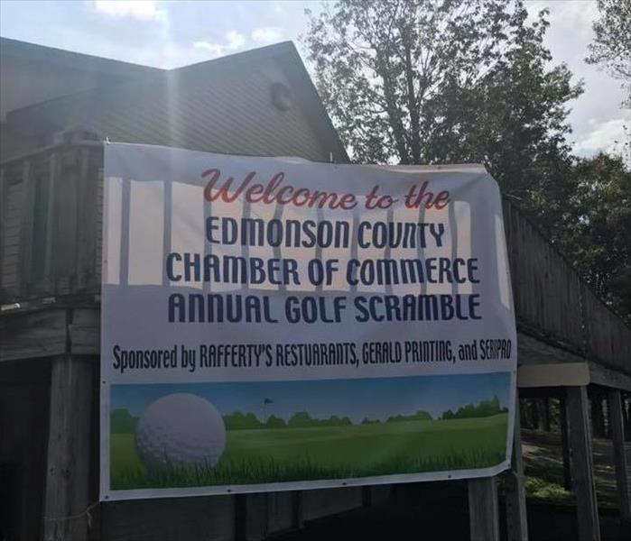 Banner for the chamber hanging on the side of the golf clubhouse introducing the sponsors and what the event is