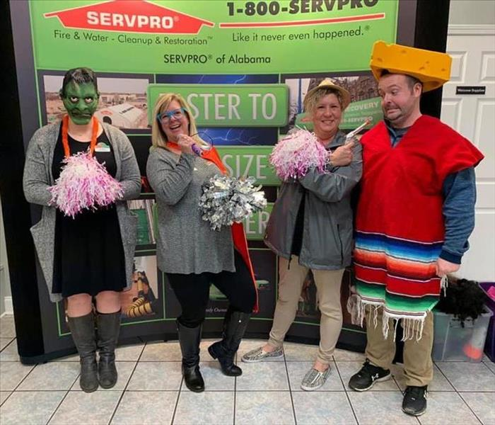 4 SERVPRO employees dressed up in front of a SERVPRO backdrop, acting crazy