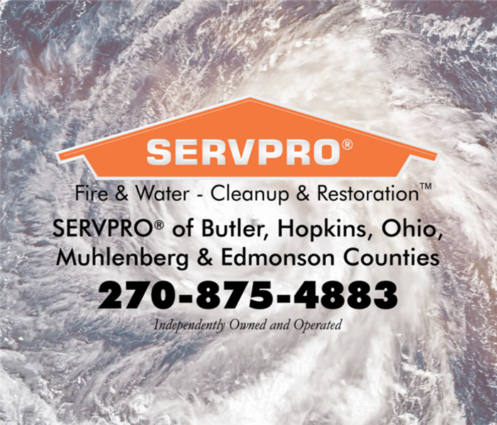 Arial view of a hurricane on the ocean with an orange SERVPRO house and contact information