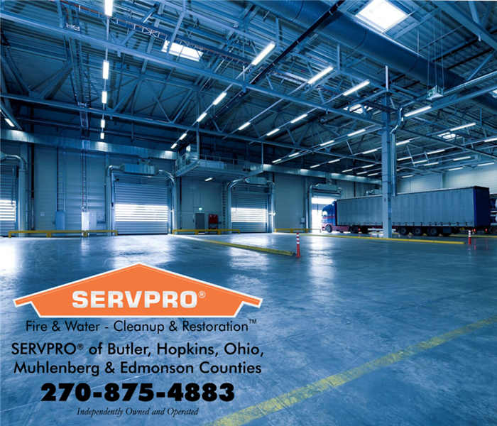 Factory with bay doors, and a truck. SERVPRO logo in corner of photo with information
