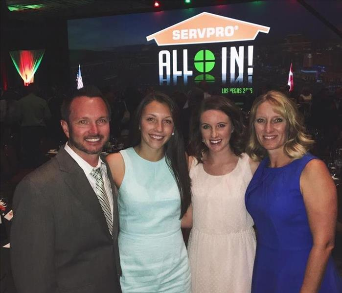 "Man and three women standing in a dark room with a SERVPRO orange house logo behind them with the words ""All In!"""